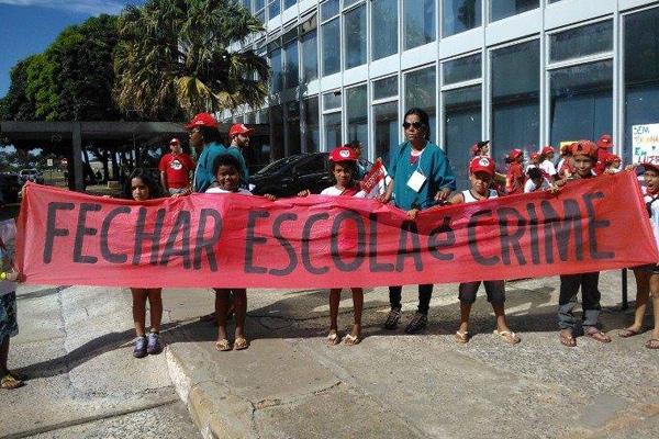"""Crianças portam faixa onde lê-se """"fechar escola é crime"""""""