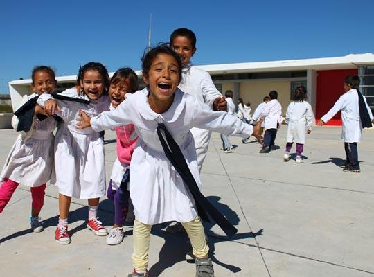 Crianças se divertem no pátio da ETC Jardines de Pando, no sul do Uruguai.