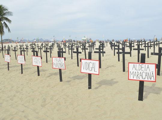 No praia de Copacabana (RJ), moradores de comunidades protestam contra remoções forçadas.