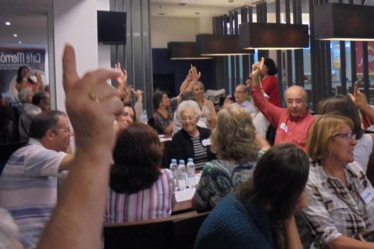 Participantes do Café Memória, com a mão levantada.