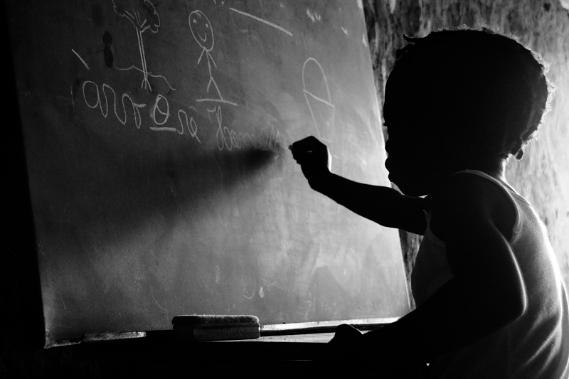 criança escrevendo em lousa na escola