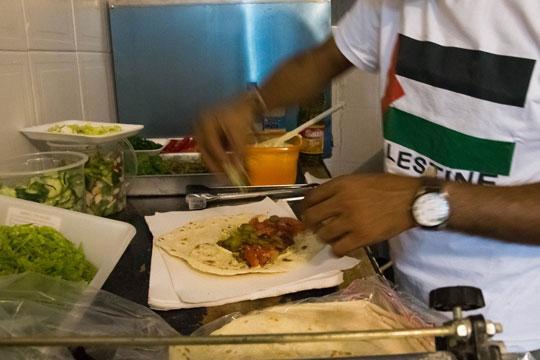 Refugiado prepara sanduíche no Al Janiah (Reprodução)