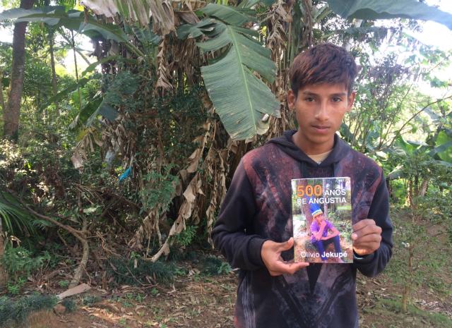 Werá exibe livro escrito pelo pai, que fala da opressão sofrida pela população indígena no Brasil.