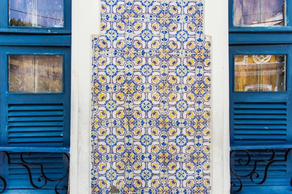 fachada de azulejos coloridos entre duas janelas azuis em Olinda