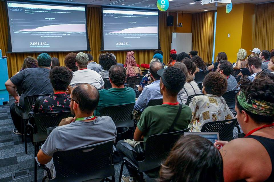 pessoas fotografas de costas assistem palestra