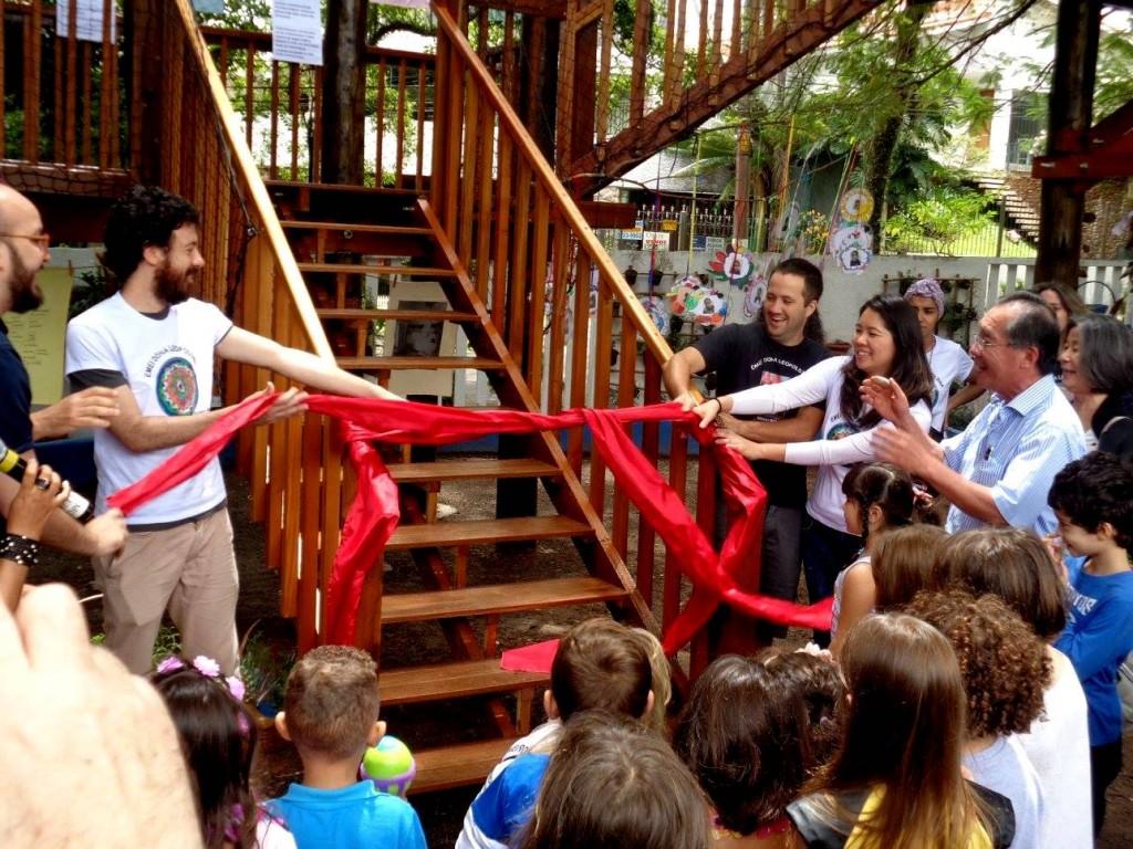 pessoas inauguram com um laço vermelho casa da árvore na escola
