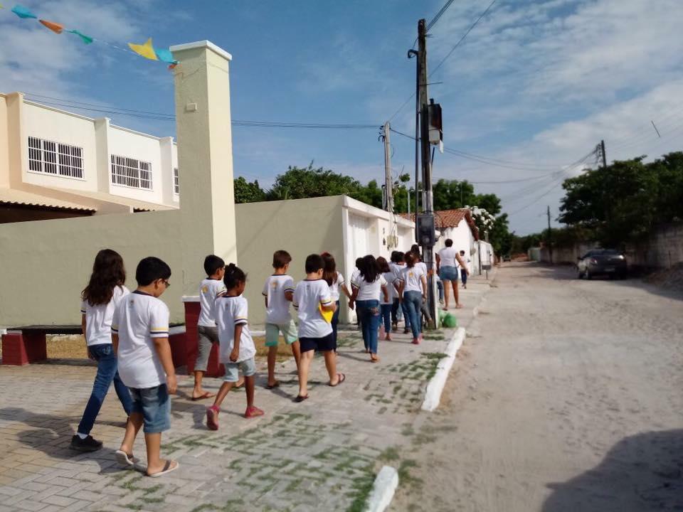 crianças de costas andando na calçada da cidade