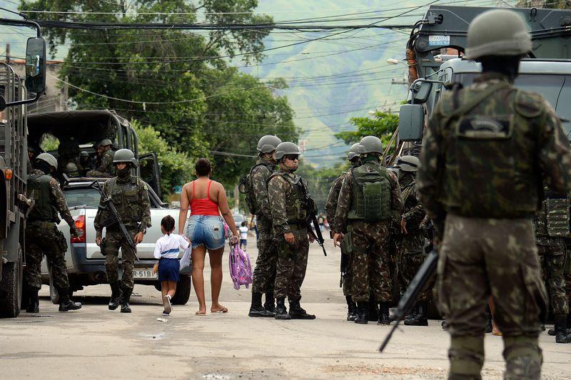 criança e mãe passam no meio de militares