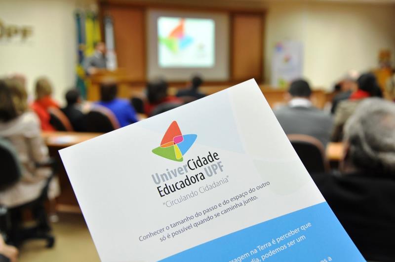 folder que tem o logo do projeto univercidade educadora sendo segurado em frente a uma plateia