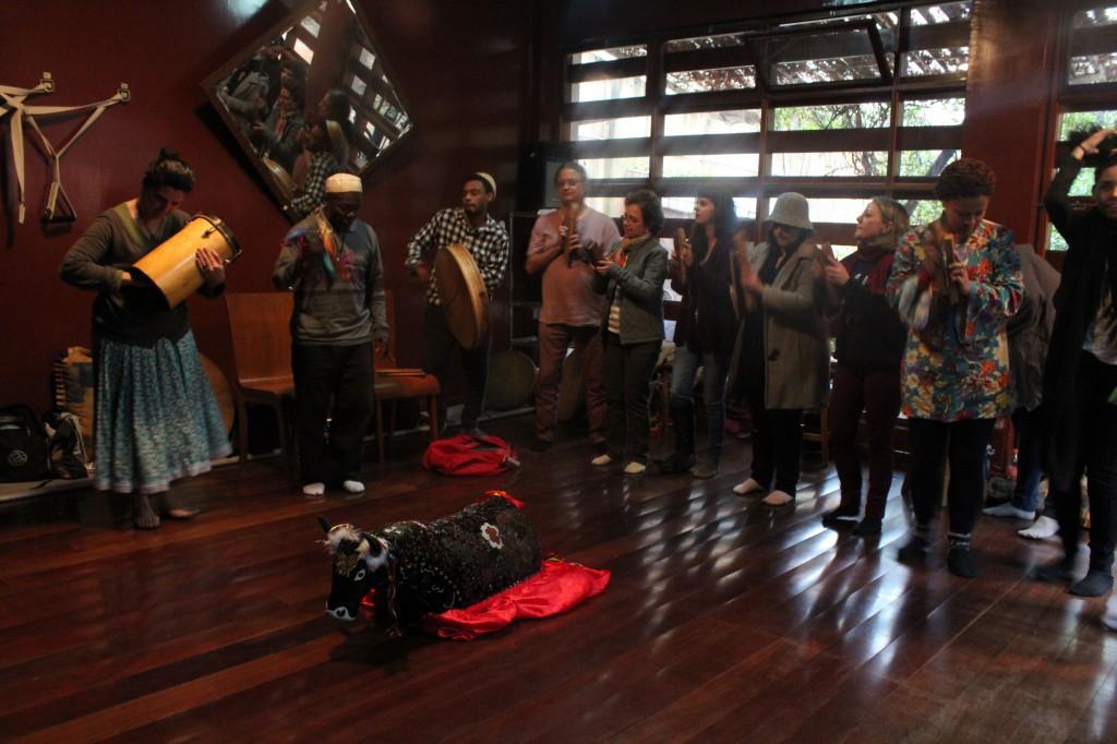 pessoas se reúnem ao redor da estátua do bumba meu boi