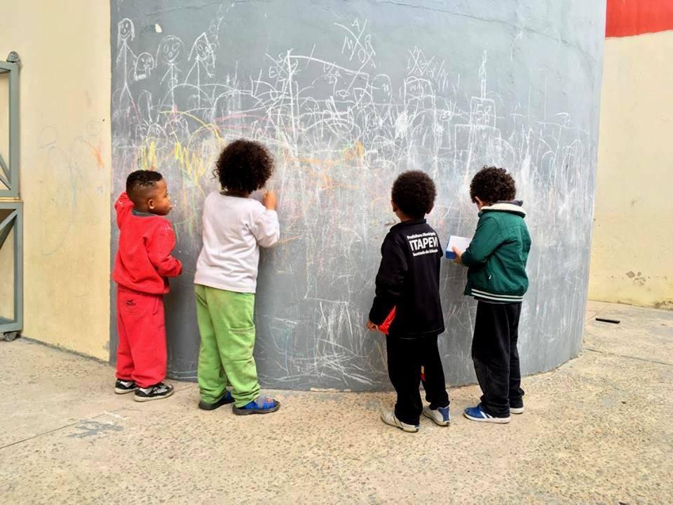 crianças brincam em estrutura cinza