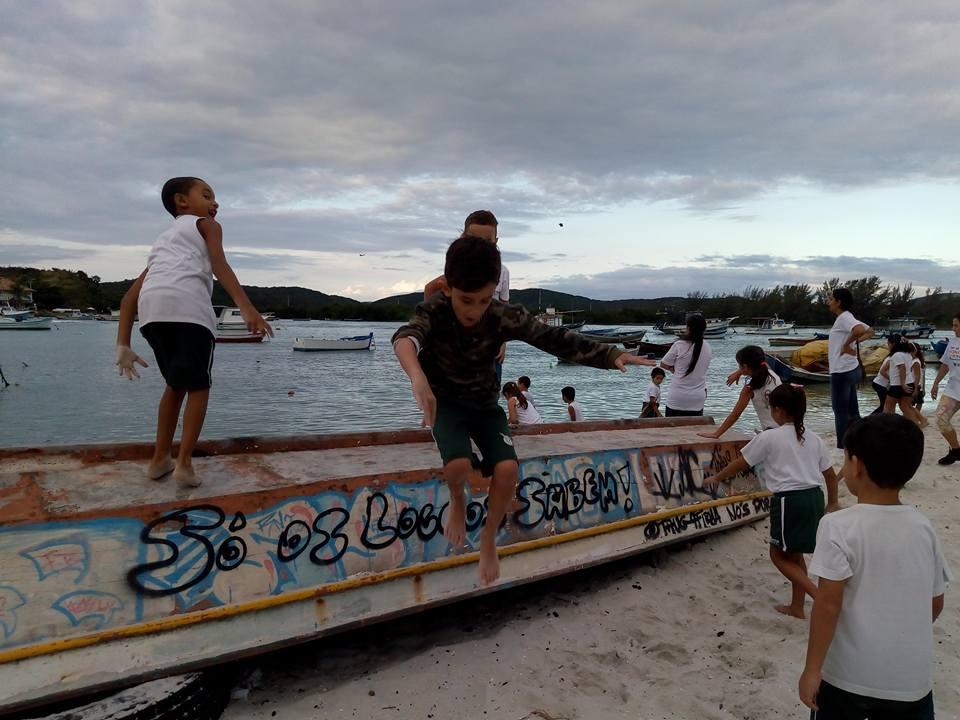 crianças brincam ao livre pulando barcos
