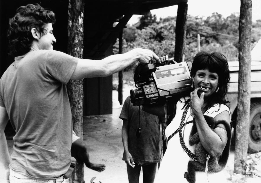 cineasta Vincent Carelli mostra para mulher indígena câmera