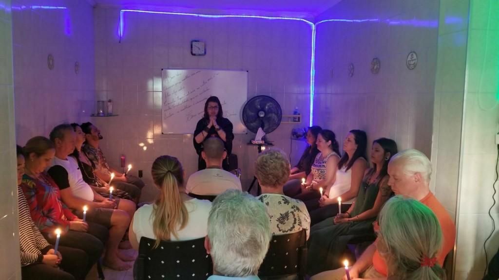 benzedeiras ministram curso para alunos numa sala com luzes azuis
