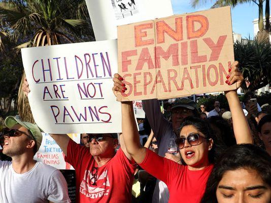 pessoas seguram cartazes contra separação das crianças