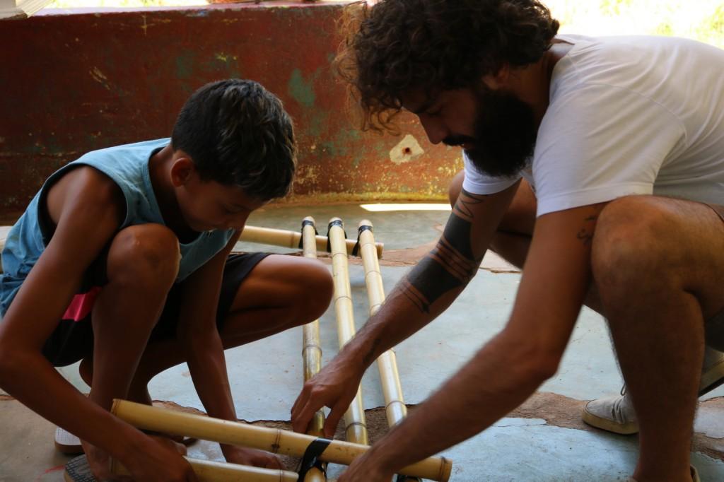 rapaz e criança trabalham com a estrutura de bambui