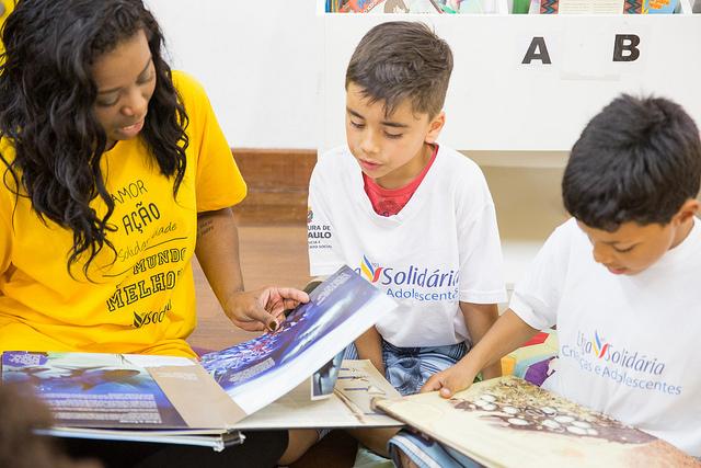 voluntária lê para duas crianças na liga solidária