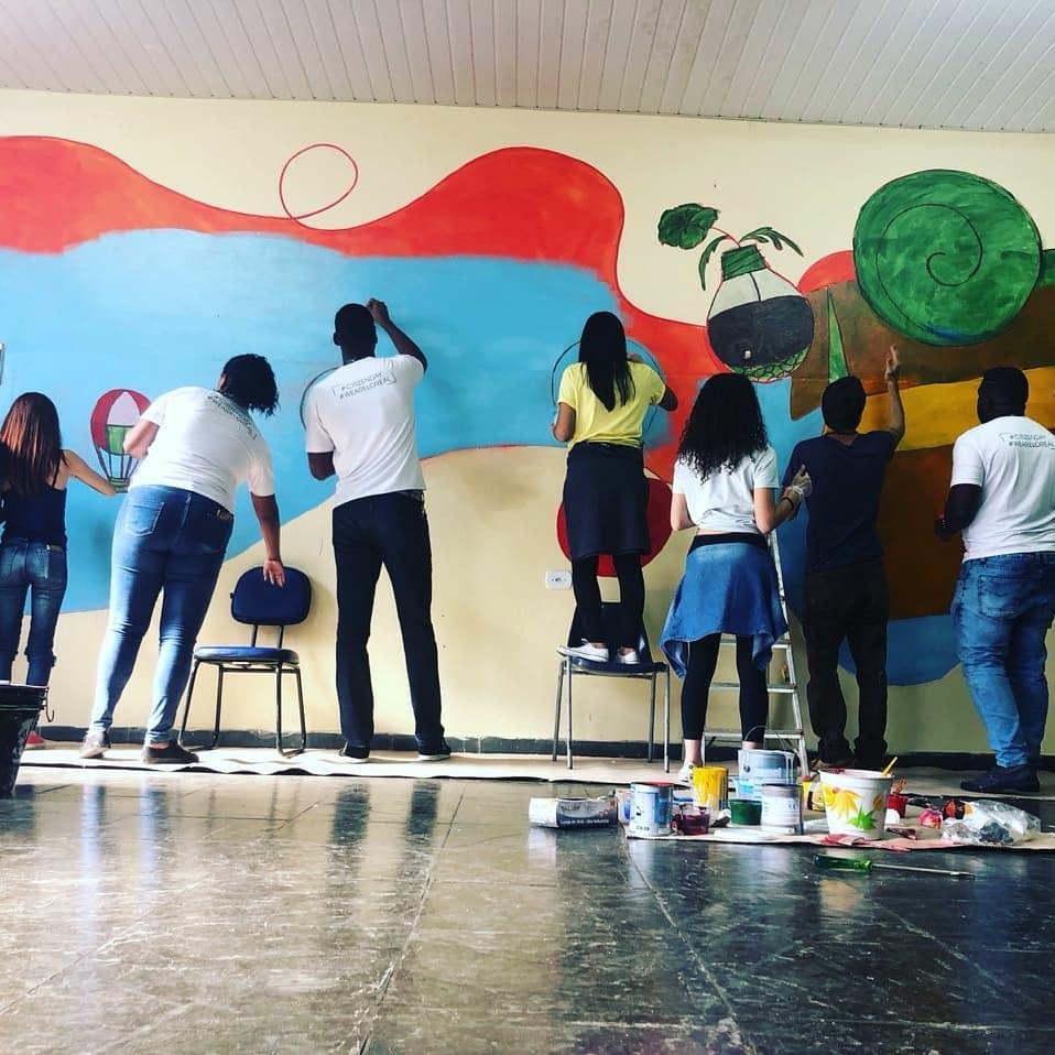 pessoas pintam a parede da liga solidária