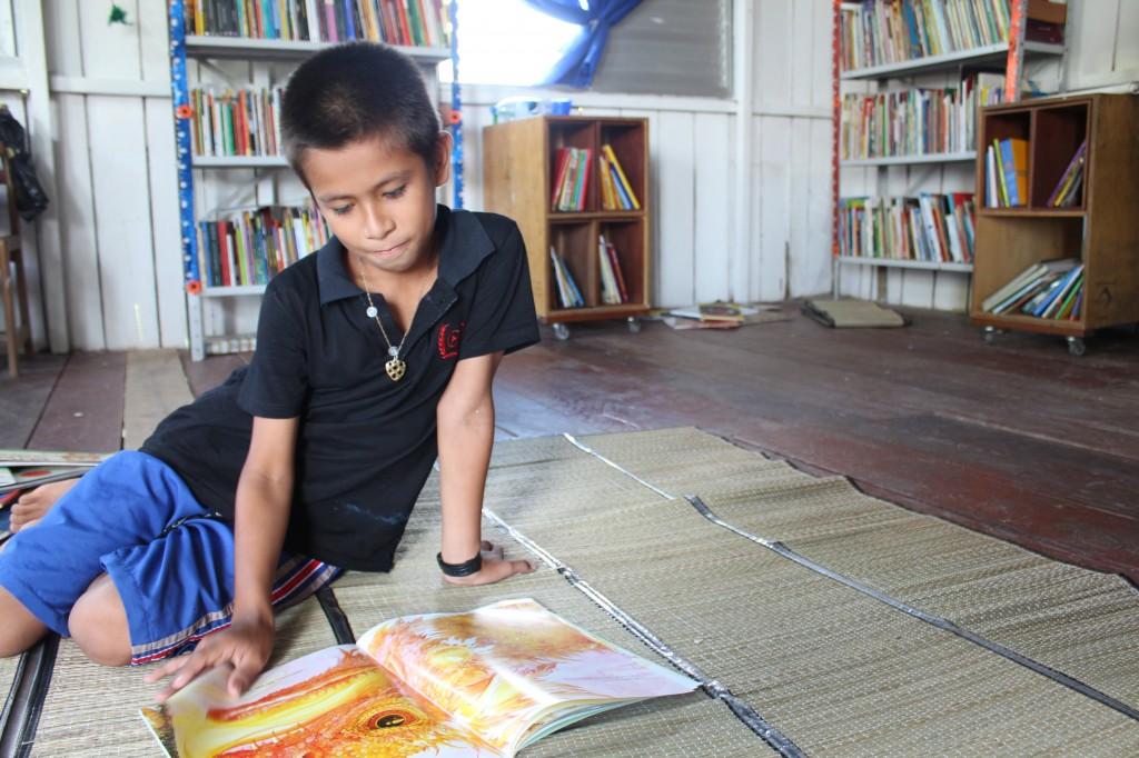 criança lê livros espalhados no chão