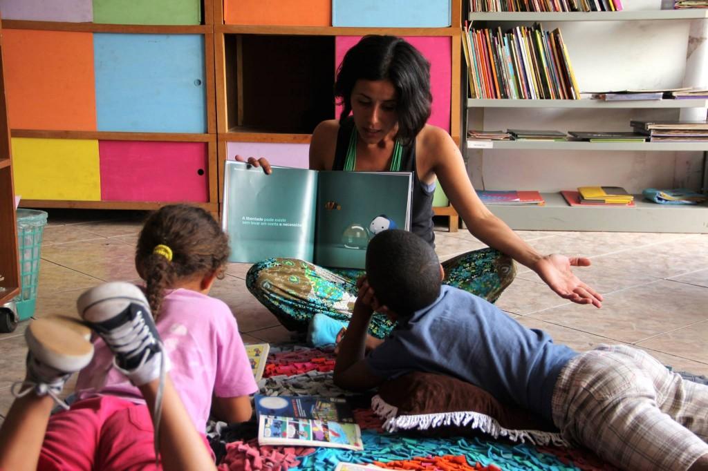 mediadora lê para crianças na sala da biblioteca