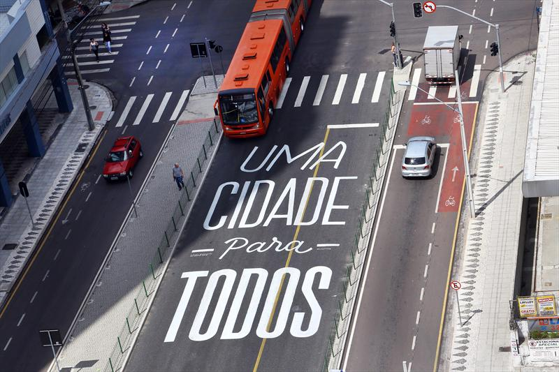 onibus passa por uma faixa que diz cidade para todos