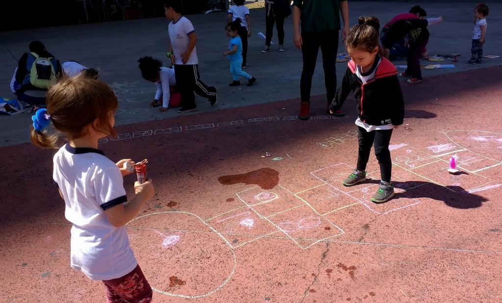 duas meninas brincam de amarelinha em um terreno marrom