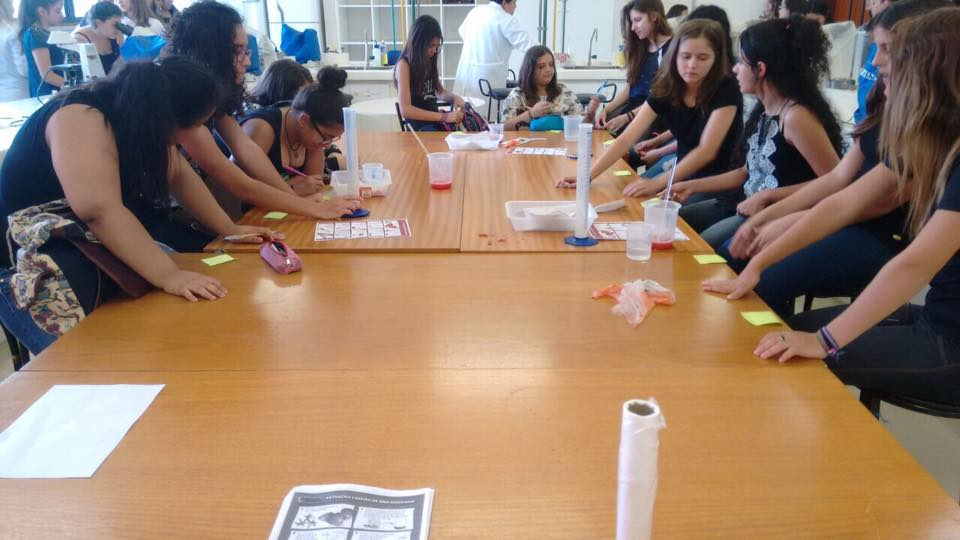 meninas se debruçam numa mesa de ciências