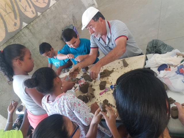 crianças esculpem argila com morador mais antigo de comunidade