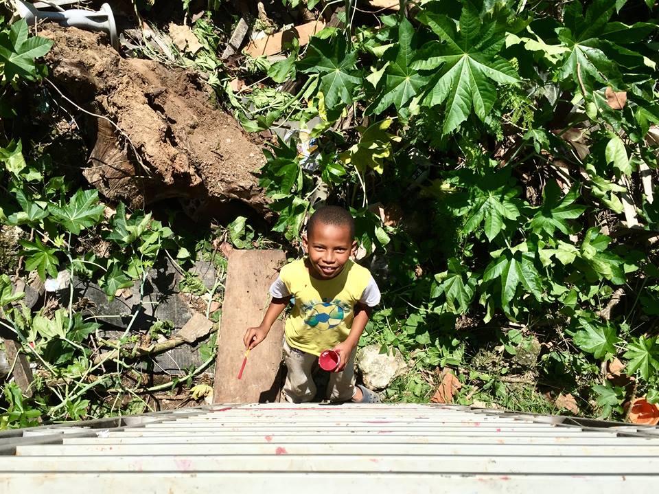 criança brincando com tinta vermelha no meio do terreno