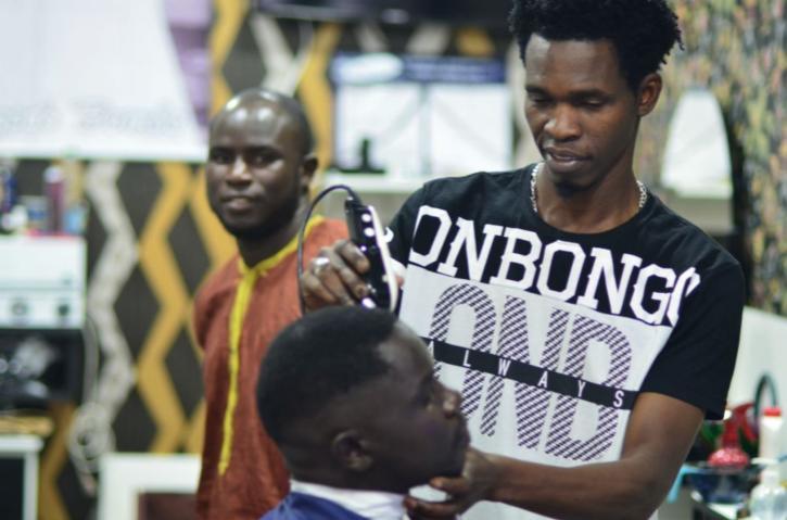 imigrante de um país africnao cortando cabelo