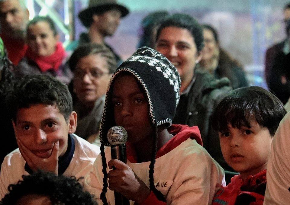 criança fala no microfone na feira literária