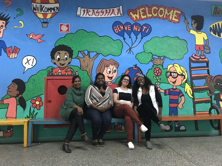 Eliane, Juliana, Camilla e Mariana em frente a um mural feito pelos estudantes