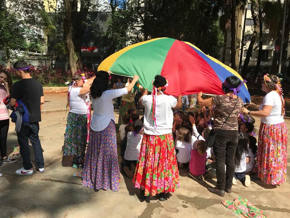 grupo de educadores cobre um grupo de crianças com uma tenda