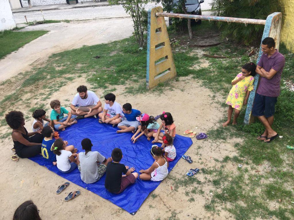 pessoas se juntam numa lona para discutir direito à cidade e infância