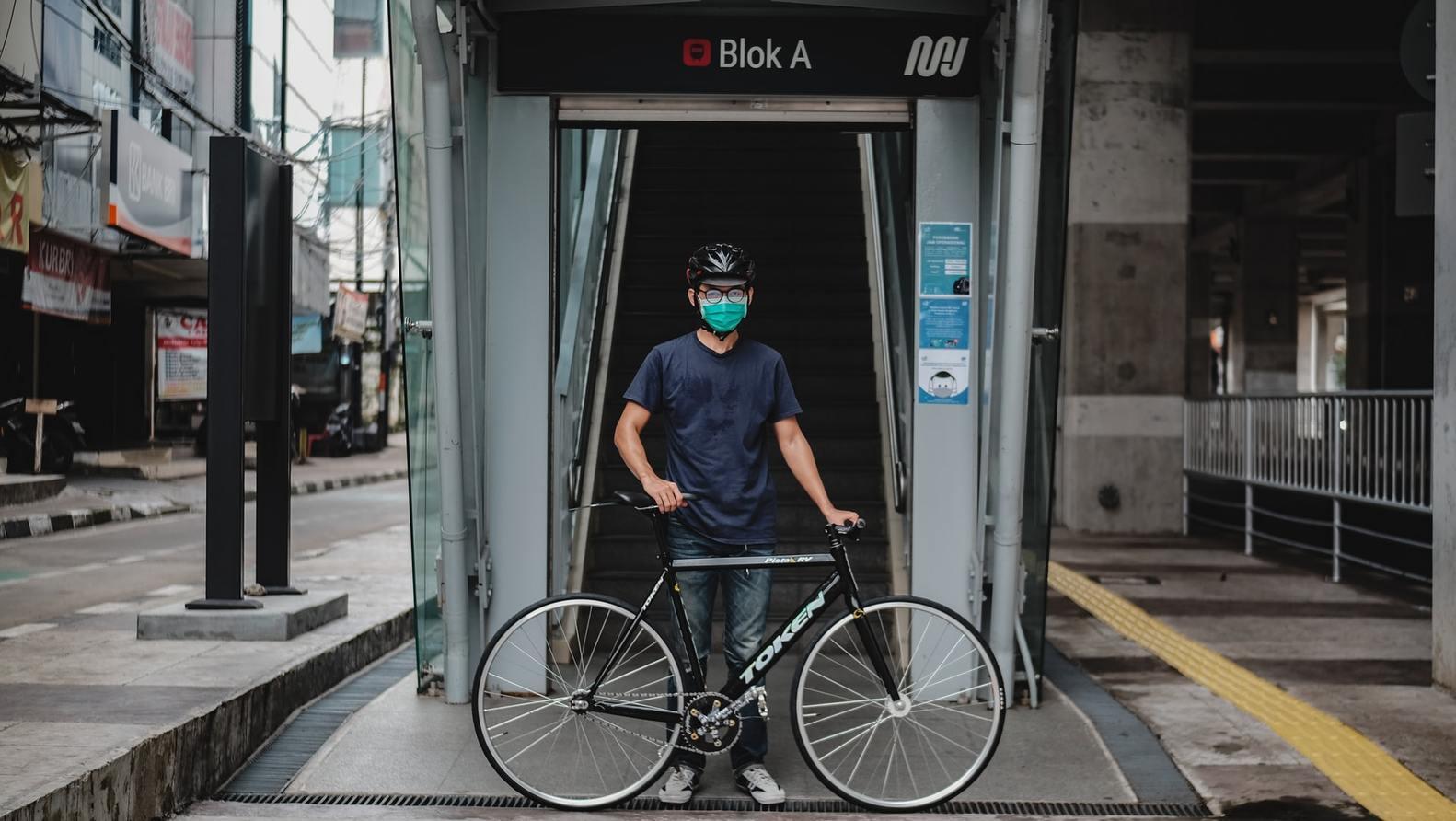ciclista com máscara na frente da entrada do metrô