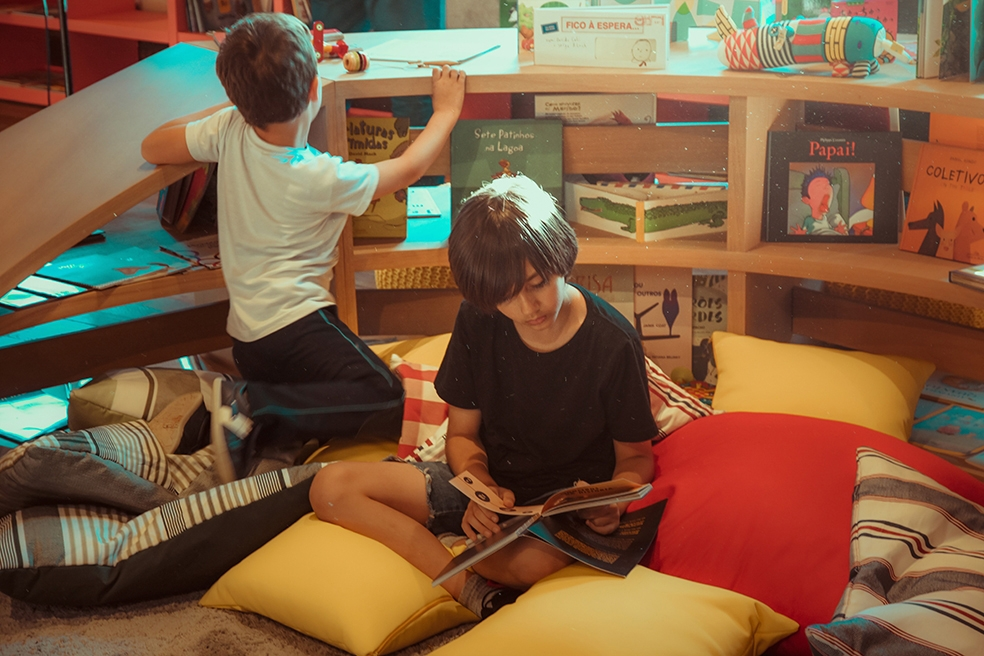 crianças leem livro e brincam no instituto de leitura quindim