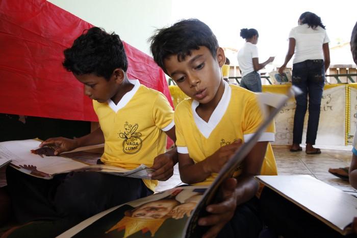 crianças leem livro na associação vagalume