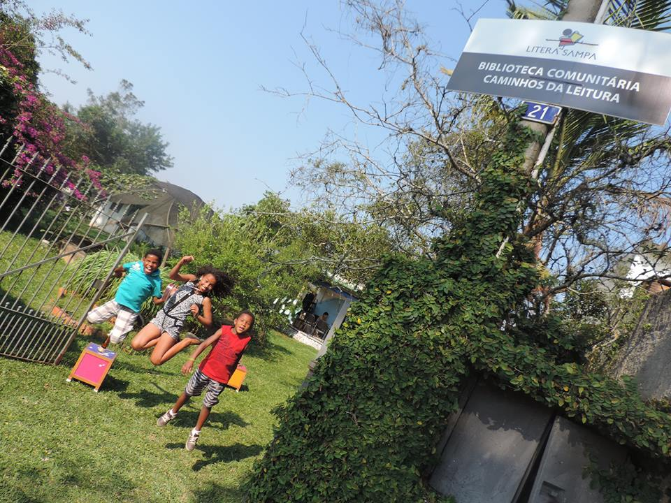 crianças na frente da biblioteca comunitária caminhos da leitura